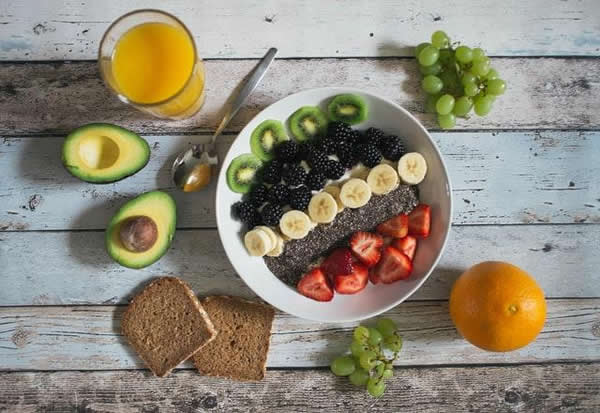 Bowl of colorful fruit with whole grain toast